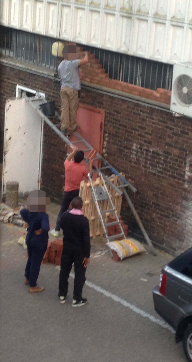 PIC FROM MERCURY PRESS (PICTURED: BUILDER BALANCING ON LADDERS THAT ARE BEING HELD UP ON A DOOR) These bizarre pictures show what could be the UKís most ëidioticí builder ñ as he balances ladders on an OPEN DOOR directly in front of another door that could open at any moment. The precarious set-up was caught on camera by Miles Davies, an industrial techno musician, as banging from the builder disturbed him recording music in Camberwell, London. The 33-year-old was stunned to discover the…