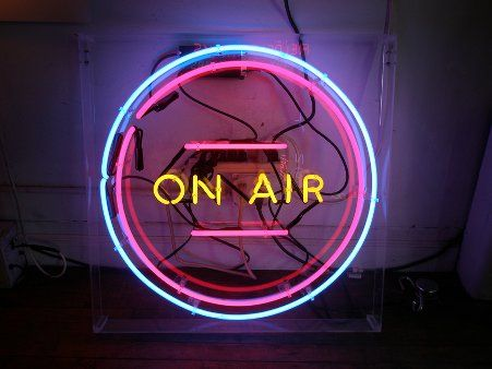 "THIS NEON SIGN HAS A LIGHT BLUE CIRCLE, A LIGHT PURPLE BACKGROUND, AND THE WORDS "" ON AIR."""