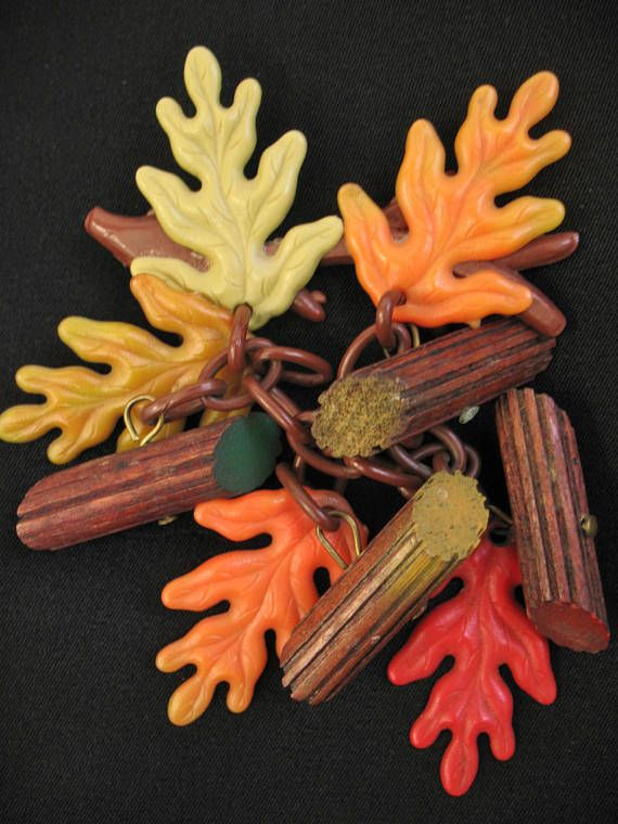 FOR YOUR CONSIDERATION is this charming 30s 40s pin featuring orange, red, green, & gold old plastic Oak leaves with logs, dangling from brown celluloid chain attached to branch.  CONDITION: Great...no issues!  SIGNATURE: None  SIZE: Broach measures 2 1/2 wide and about 4 long (top to