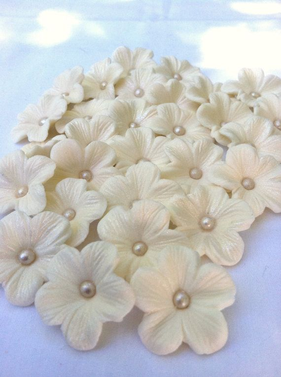 Edible white gum paste cherry blossoms with an ivory dragee in the middle and then pearl dusted to give them a shine.  A little addition to a cake or cupcakes you are decorating...for weddings, birthdays, parties.