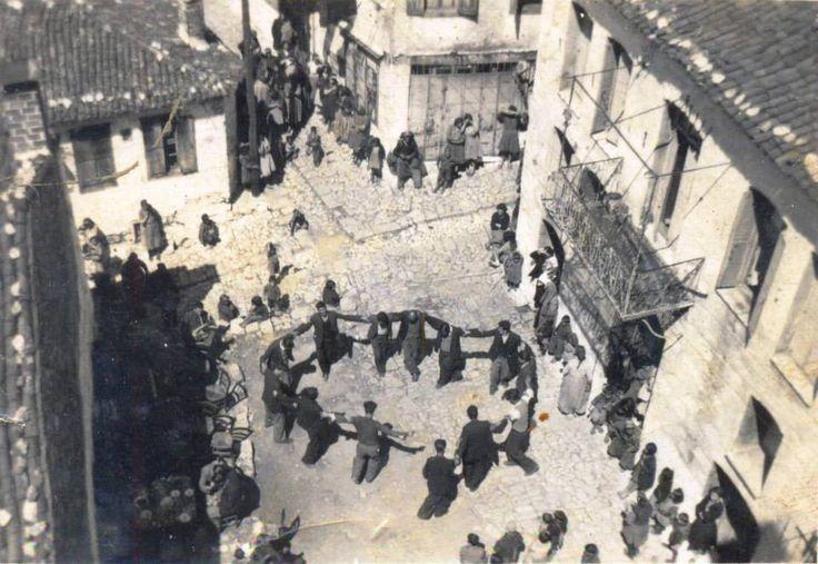 Αγιάσος-Λέσβος Φωτογραφια τραβηγμένη από την ταράτσα του Νέου Ξενώνα της Παναγίας (σημερινό κτίριο Αστυνομίας). Στο σταυροδρόμι χορεύουν και γλεντούν. Η περιοχή λεγόταν «Χουρεύτιργια». Εκεί ήταν παλιά ένα από τα γραφικά κουτούκια του χωριού. Το σπίτι δεξιά είναι το παλιό πανδοχείο της Πόμπινας. Το ένα λιθόστρωτο (σημερινή οδός Εθνικής Αντίστασης) κατεβαίνει από τον Ταξιάρχη και το άλλο (σημερινή οδός Ειρήνης) είναι αυτό που πάει προς την Αγία Τριάδα.  * * *