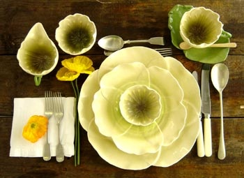 A fun place setting of yellow flowers, all the way to a tea cup on a green leaf!
