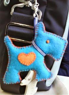 Perro de fieltro en color turquesa con un corazón naranja. Felt dog.