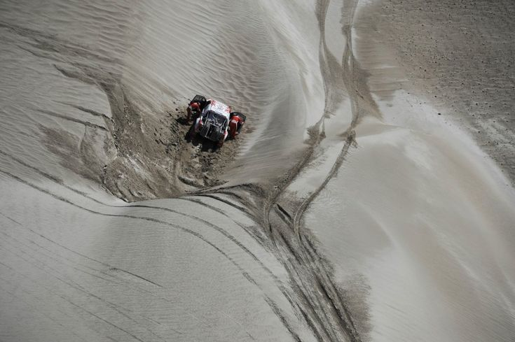 Toyota's driver Giniel De Villiers, from South Africa, and co-driver Dirk Von Zitzewitz, from Germany, try to push their car after it went off the road during the fifth stage of the 2012 Argentina-Chile-Peru Dakar Rally between Chilecito and Fiambala in Argentina. (AP)