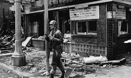 A national guardsman amid the rubble following the Watts riots, Los Angeles, California, August 1965. Photograph: Hulton Archive/Getty Images