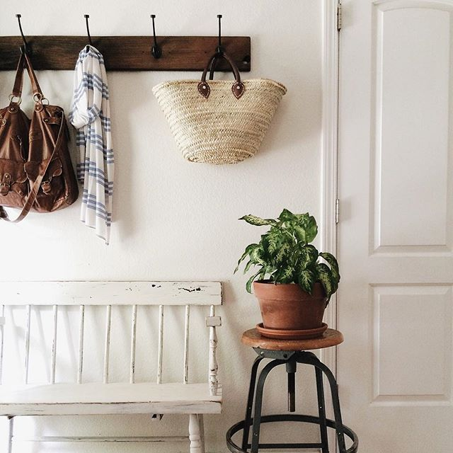 Entryway | Seating + Decor - Lovely High-back Rocking Chair-like bench with a metal and wood swivel stool to hold potted plants. DIY worthy coat rack with baskets, bags and scarves hanging.