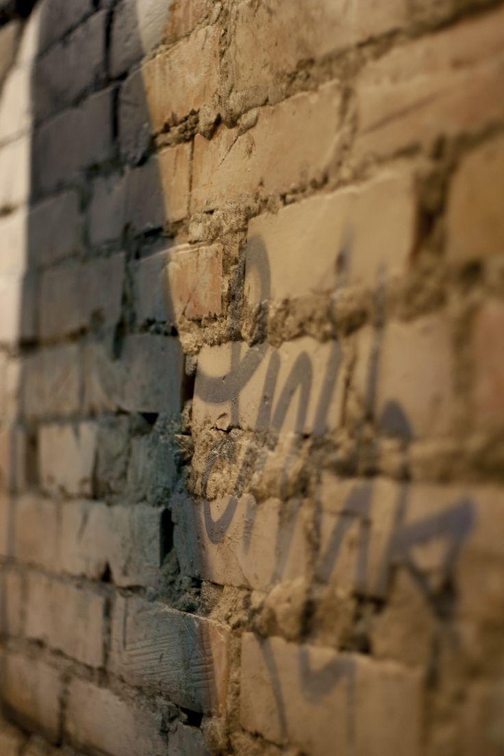 """Un open space ricavato dalla demolizione di tre tramezzature che definivano un bilocale. Lo spazio è caratterizzato da una forte simmetria nella composizione dei volumi e delle illuminazioni artificiali. L'ambiente è contaminato da influenze """"street art"""", come si può notare dal grande graffito che occupa due lati della zona soggiorno e dalla volontà di recuperare l'estetica della parete in mattoni originale. Enko"""