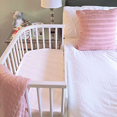 bedside sleeper which attaches to bed showcased in a Nursery