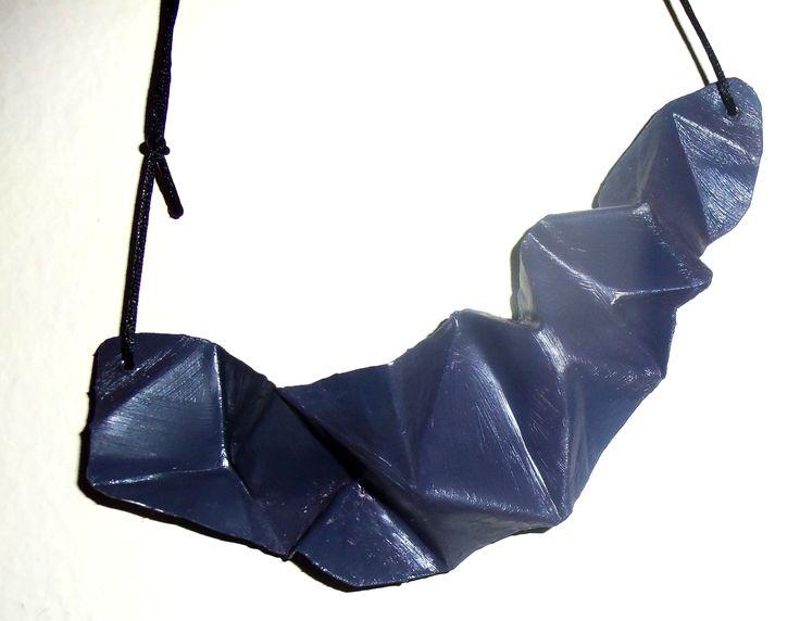 Ασύμμετρο πολυεδρικό κολιέ από φύλλο αλουμινίου βαμμένο σε ψυχρό μοβ-ανθρακί χρώμα. Τα κορδόνια ρυθμίζονται στο επιθυμητό μήκος.