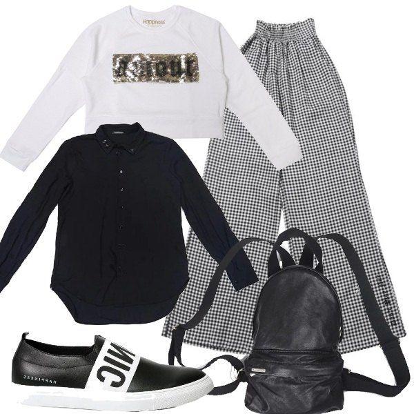 La camicia nera lunga esce dalla felpa a top con stampa frontale a pailletes dorate. Pantaloni a scacchi bianchi e neri modello a palazzo con elastico in vita. Sneakers basse bianche e nere, mini zaino.