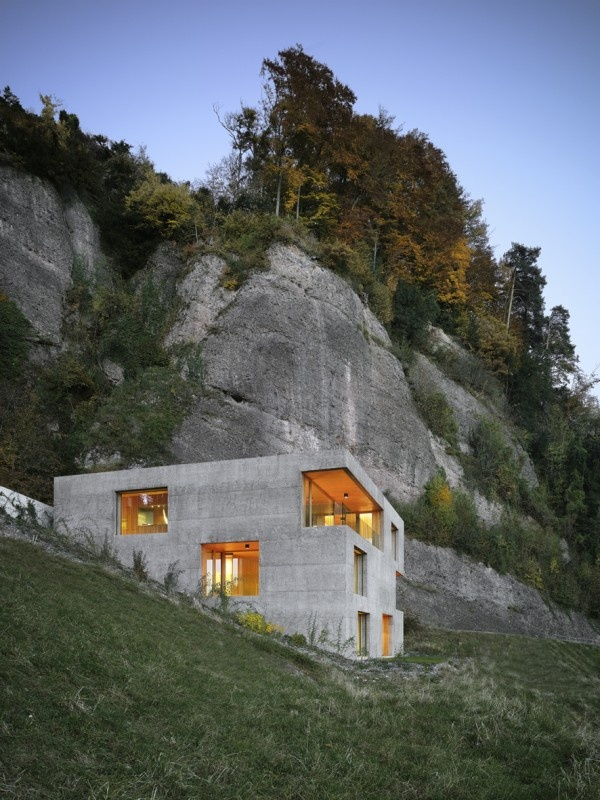 Overlooking Lake Lucerne in Switzerland, House Vitznau designed by Lischer Partner Architekten is a timber house - larch wood is used internally for floor and ceiling finishes - concealed within a concrete shell that blends into its rocky backdrop.
