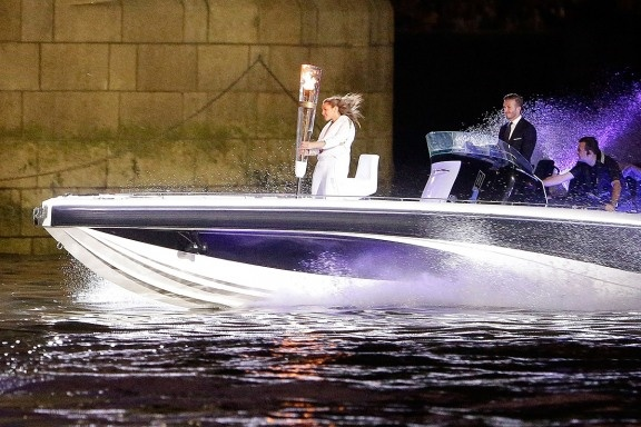 David Beckham passes under London's Tower Bridge driving a speedboat named Max Power, which carries the Olympic torch and its torchbearer, on July 27, 2012.