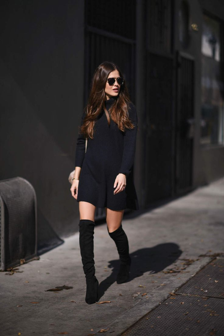 Paola Alberdi wears thigh high boots with a minimalistic black sweater  dress, creating a casual