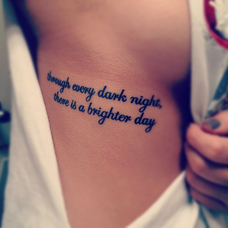 Chica mostranto su tatuaje que esta bajo su seno con una frase en ingles
