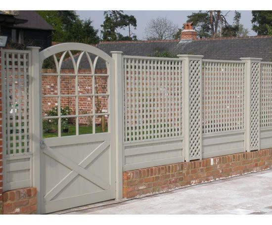 Trellis painted in muted colours harmonises with old brick wall