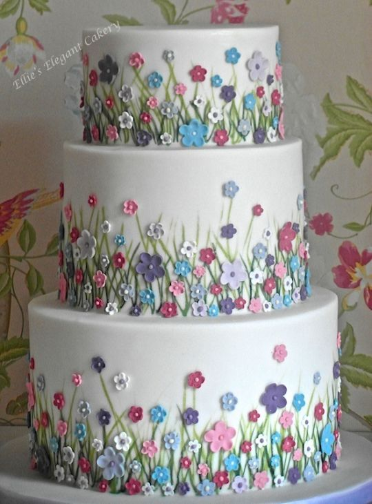 Simple and elegant with lots of colourful meadow flowers. Originally the cake was just going to be little flowers, but just before I made it I had the idea of adding grass to make it more meadow like. The bride and groom loved the idea and I am so...