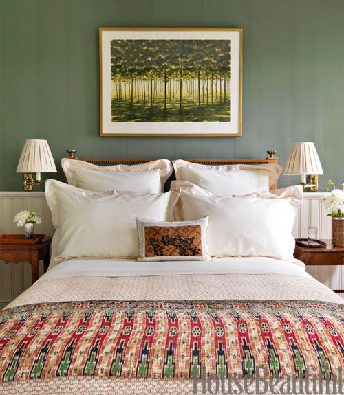 "An April Gornik painting is set off by walls in Tavern Green by The Old-Fashioned Milk Paint Co. in a bedroom of this East Hampton home by designer Bunny Williams. An Indonesian quilt adds texture ""and a Deco feeling.""   - HouseBeautiful.com"