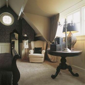Slaapkamer in Engelse stijl met oor fauteuil en woonaccessoires in Engelse stijl.