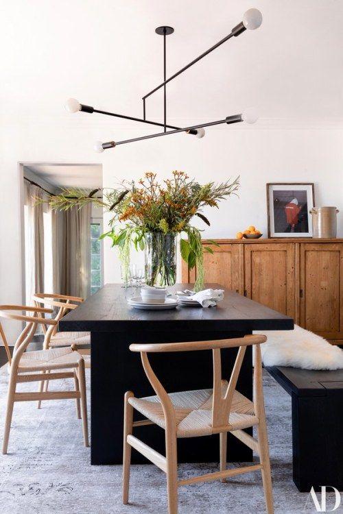Modern light fixture above dark wood dining table Dining Rooms in