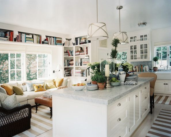 Mark D. Sikes & Michael Griffin's kitchen island topped with potted plants and hurricane vases