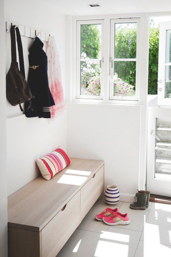 I entreen har parret tegnet et praktisk opbevaringsmøbel. Det er i eg som køkkenelementerne og lavet af Søgaard Møbler. Et godt tip er at holde sig til en enkelt træsort i indretningen af et rum. Det giver mere ro.