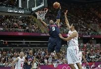 USA's Andre Iguodala (9) towers over Tunisia's Mohamed Hadidane as he slam dunks during a men's basketball game at the 2012 Summer Olympics, Tuesday, July 31, 2012, in London.