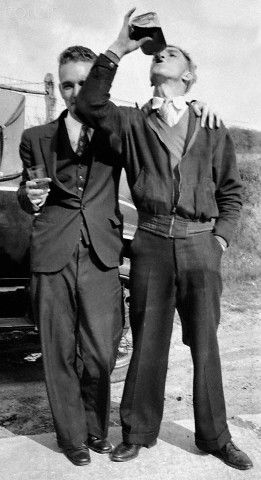 Two young men enjoy some whiskey from a flask in 1930s prohibition-era Maryland. ca. 1930