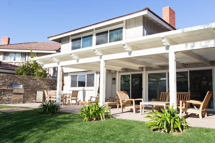 White wooden pergola covers a brick paved floor. Barbecue in the background. What kind of parties would you throw here?