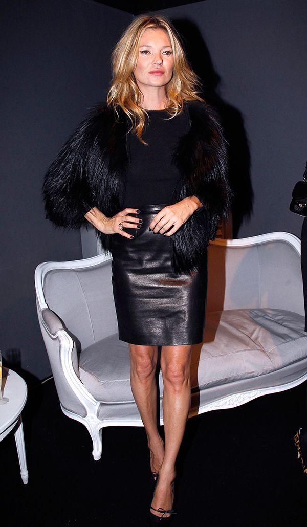 Kate Moss usa mini saia de couro no frio com blusa preta, casaco de pelos preto e scarpin preto