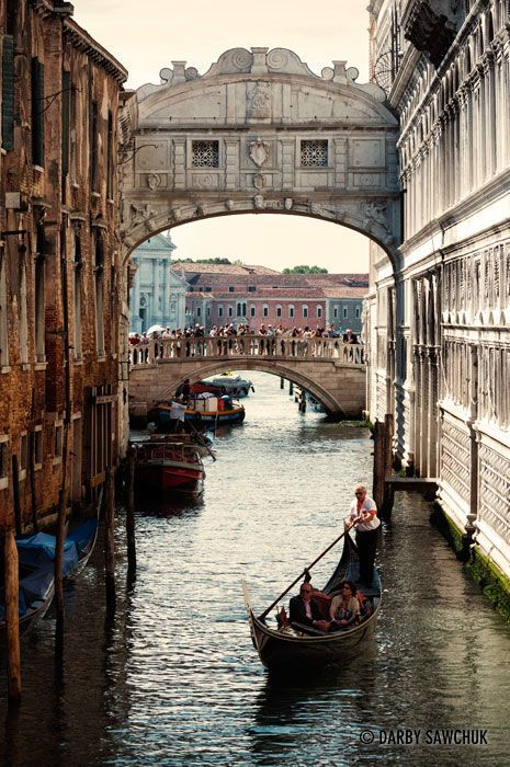 A gondola glides under the Bridge of Sighs while tourists admire the view in the background.