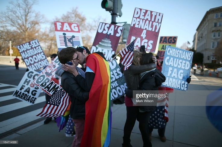 Two same sex couples kiss in front of Westboro Baptist Church protesters, at the U.S. Supreme Court, on March 27, 2013 in Washington, DC. Today the high court is scheduled to hear arguments on whether Congress can withhold federal benefits from legally wed gay couples by defining marriage as only between a man and a woman.