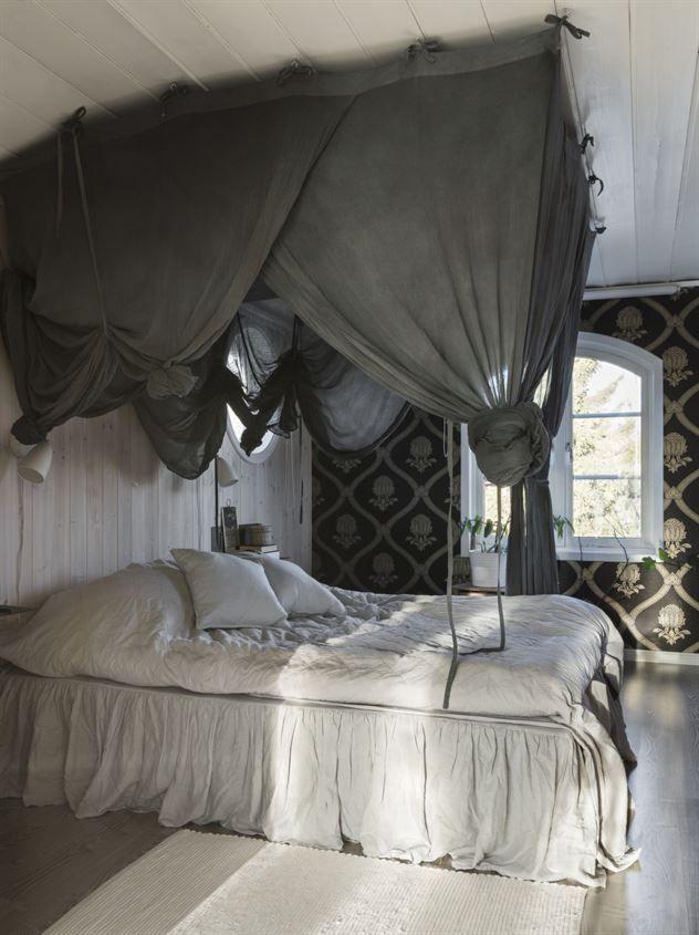 Tapeten i bakgrunden kommer från William Morris. Sängen är från Boom inredning. Säng- himmeln är infärgad med textilfärg, den och sängkappan är från Ellos. Kuddar i linne från H&M home. Sänglamporna är från Lampan.se.
