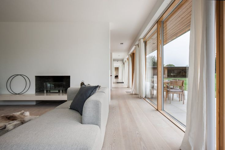 The corridor allows for views that extend the entire length of the home. Tagged: Living Room, Light Hardwood Floor, Sectional, Gas Burning Fireplace, Recessed Lighting, and Rug Floor.  Photo 172 of 13553 in Best Photos from A Scandinavian-Style Pavilion in England Is Listed For $2.1M