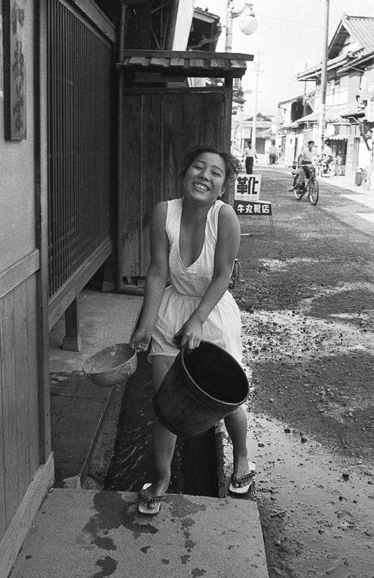はじらい. Woman carrying buckets and smiling. Japan 1956.