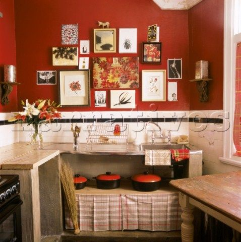 Red eclectic kitchen detail with pictures and saucepans