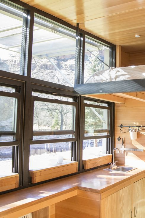 A large window wall allows the tiny house occupants to connect with nature with an unobstructed view of their surroundings.