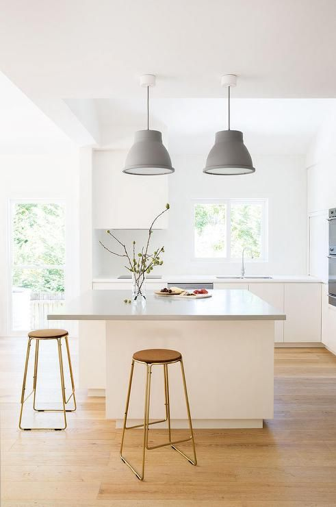 Modern kitchen boasts a pair of gray pendants illuminating a white kitchen island topped with gray quartz lined with backless gold counter stool with cork seats.