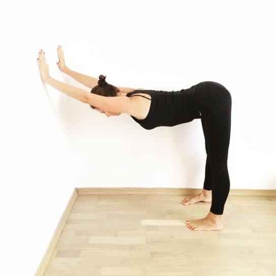 Sposób na przykurcze w tyłach nóg, ból pleców i napięcie w barkach - uttanasana z rękami na ścianie.