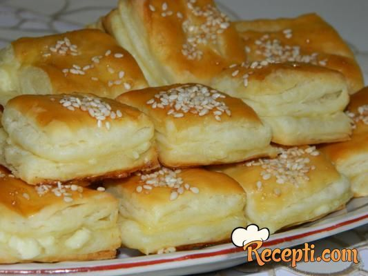 Recept za Lisnato pecivo sa sirom. Za spremanje peciva neophodno je pripremiti brašno, mleko, vodu, kvasac, šećer, so, ulje, margarin, sitan sir, jaja, susam.