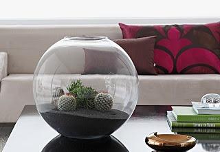 O globo transparente chama atenção na mesa de centro, com um microjardim de cactos e suculentas. Autora da montagem, a designer de jardim Caroline Saccab Haddad Zakka, da Secret Garden, usou uma base de areia preta para encaixar os vasinhos plásticos.