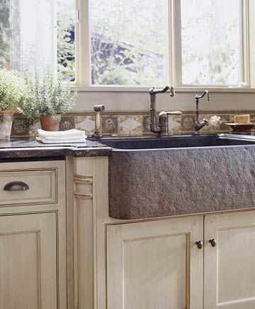 Stone Farmhouse Sink- An upscale kitchen-remodeling project features a rugged apron-front sink that was carved from a single piece of honed granite. The dark sink stands out against the taupe cabinetry and dark granite countertops.