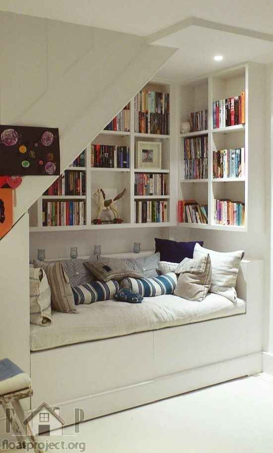 Reading nook under stairs -- built-in seating (guest bed?) and bookshelves
