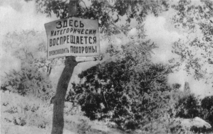 """In the blooming countryside, a sign reads: """"The burial of corpses is strictly forbidden here!"""""""