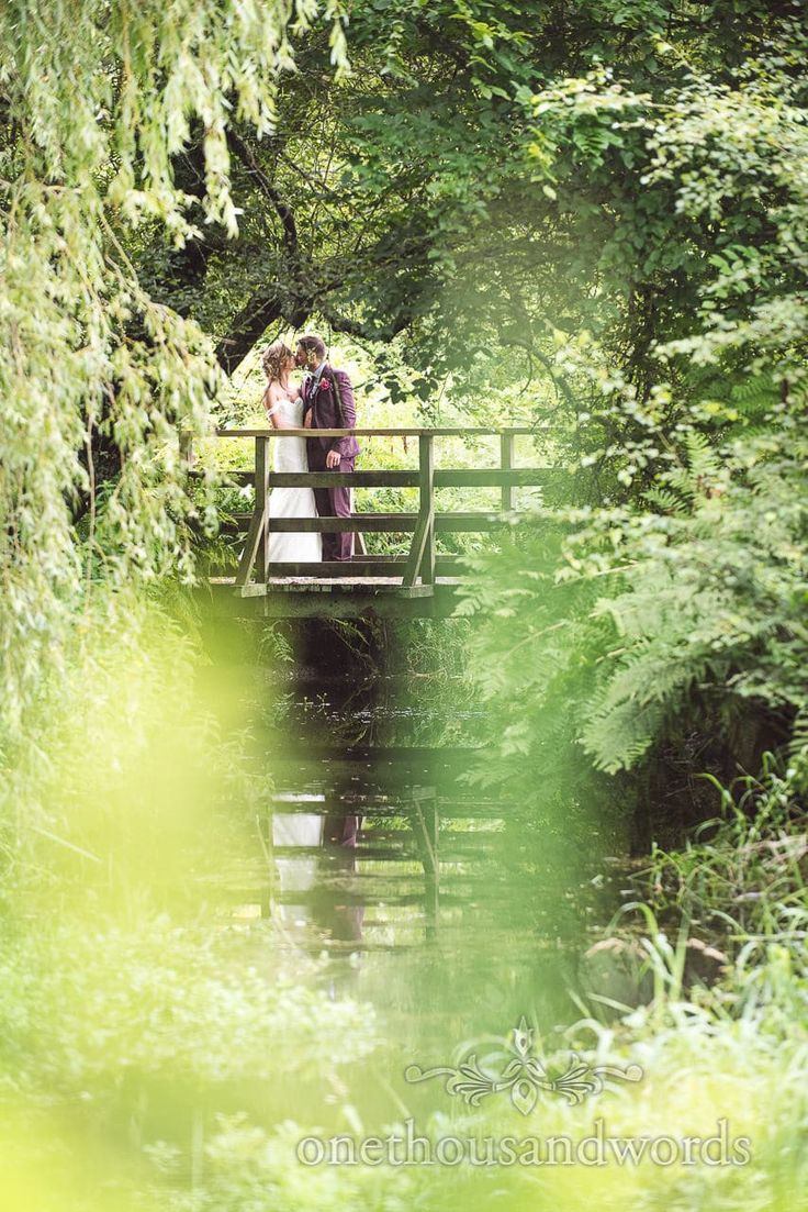 Bride and groom kiss on bridge above river at Morten Walled Gardens Wedding. Photography by one thousand words wedding photographers