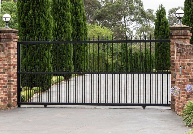 Modern and secure sliding gate in metal/ wrought iron. Powder coated black finish set between two brick walls.
