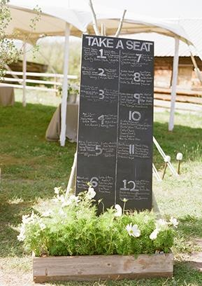 Seating chart written on chalkboard made from wooden door (maybe...or other slab of wood?)