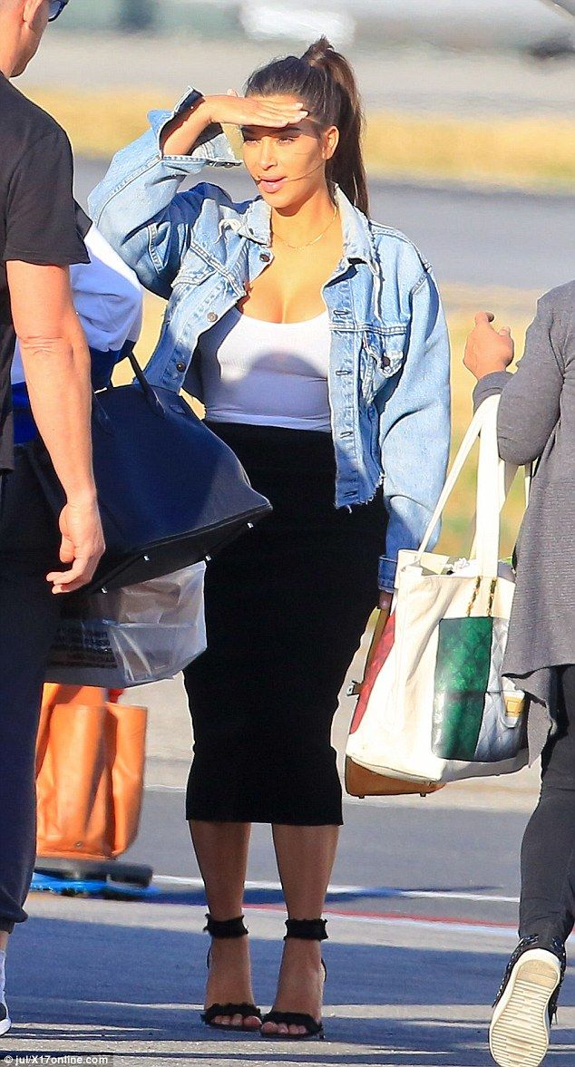 Kim Kardashian shows off her famous decolletage in low-cut top and Kanye's 'Pablo' jacket as the family arrive back in LA | Daily Mail Online