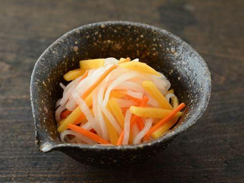 """大根とにんじんを使った定番の「なます」に甘みのある柿を合わせることで、見た目も味わいもちょっと上品に仕上がります。[product id=""""konbutsuyu-shirodashi""""]「ヤマサ昆布つゆ白だし」[/product]を使えば、素材の色合いを残したまま、美味しく仕上げることができます。"""