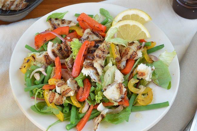 Lauwwarme salade met tilapiafilet. Gegrilde vis en boontjes gaan heel goed samen en maakt een gezonde maaltijd.