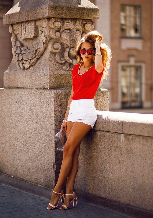 Comprar ropa de este look:  https://lookastic.es/moda-mujer/looks/camiseta-con-cuello-barco-pantalones-cortos-sandalias-de-tacon-cartera-sobre-pulsera/2319  — Pantalones Cortos Blancos  — Sandalias de Tacón de Cuero Beige  — Pulsera Dorada  — Camiseta con Cuello Barco de Seda Roja  — Cartera Sobre Transparente